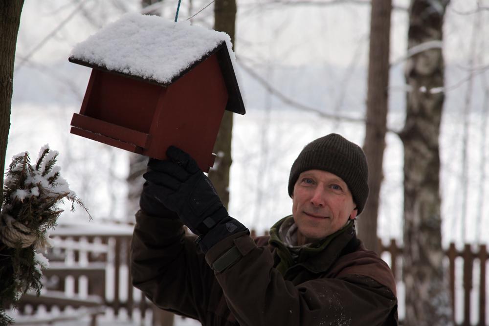 """Paul Segersvärd tarkistamassa lintulautaa; onko siellä tarpeeksi apetta ja onko """"mökki"""" siisti. Kuva: Taina Tervo"""